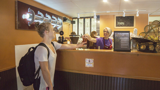 Kate Simonet, a Winona State student, grabs a coffee at Mugby Junction. (Photo by Susan Torkelson)