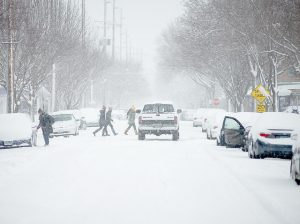 Pedestrians cross the street during a snow storm in Winona Tuesday, Feb. 2. Pedestrian Safety has been a major topic of discussion since Winona State University student Britney Nelson was hit by a driver in early November. (Photo by Jacob Striker)