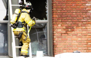 """Winona firefighter fights the flames downtown at KidSport. Taken from the Winonan's Sept. 17, 2014 article """"Downtown fire brings woes to another local business"""" by Samantha Stetzer. (Photo Taylor Nyman)"""