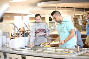 Students Claire Wass (left) and Nikko Aries (right) test out the salad bar at the newly renovated Jack Kane Dining Hall on main campus. (Photo by Kendahl Schlueter)