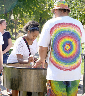 """Student Dedra Robertson decorates a vinyl record during UPAC's """"Spin Magic"""" event by the gazebo on campus Tuesday, Oct. 11. (Photo by Kendahl Schlueter)"""