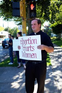 Father Jonathan Fasnacht, Chaplin of the Neuman Center, stands with National Life Chain pro-life protesters Oct. 2. He has participated in Pro life events since age 11.