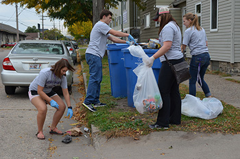 Left to right: Jessica Lavorata, Domenic Ogno, Mariah Miller and Danielle Wagner pick up an overturned trash can on Sunday during the 2016 Homecoming Clean Sweep. They volunteered with the club Circle K International. (Photo by Nicole Girgen)