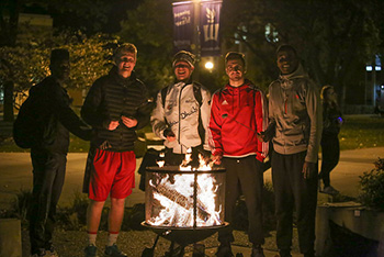 Students warm up on a cool night at the S'mores & More Bonfire, an event held outside the library on Wednesday, Oct. 12.