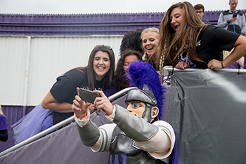 Students take a selfie with Wazoo during the first quarter of the homecoming football game on Saturday.