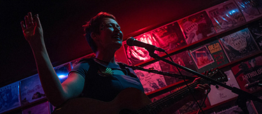 Winona State University alumna Kim Schneider plays her guitar during the Treedome Productions event held on Saturday at Broken World Record bar in downtown Winona. (Photo contributed by Adam Nantz)