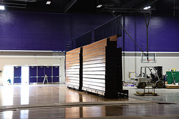 The previous wooden bleachers remain standing, along with other temporary bleachers, in the newly renovated McCown Gymnasium to provide seating until the new ones are installed. (Photo by Nikko Aries)