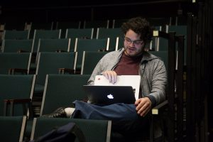 """Kort Lindblad stage manages his senior capstone project in the Black Box Theatre of the Performing Arts Center Monday evening. Lindblad wrote, produced and stage managed his own work, """"Morning, Noon & Night."""" (Photo by Taylor Nyman)"""
