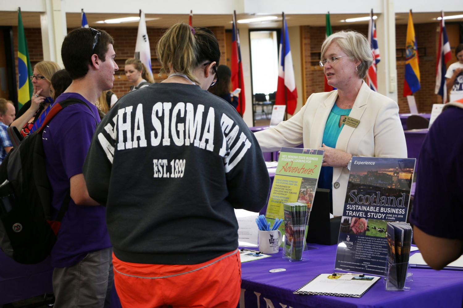 Assistant professor Jana Craft talks with students at the business administration department table. The department is offering three different travel study programs this year.