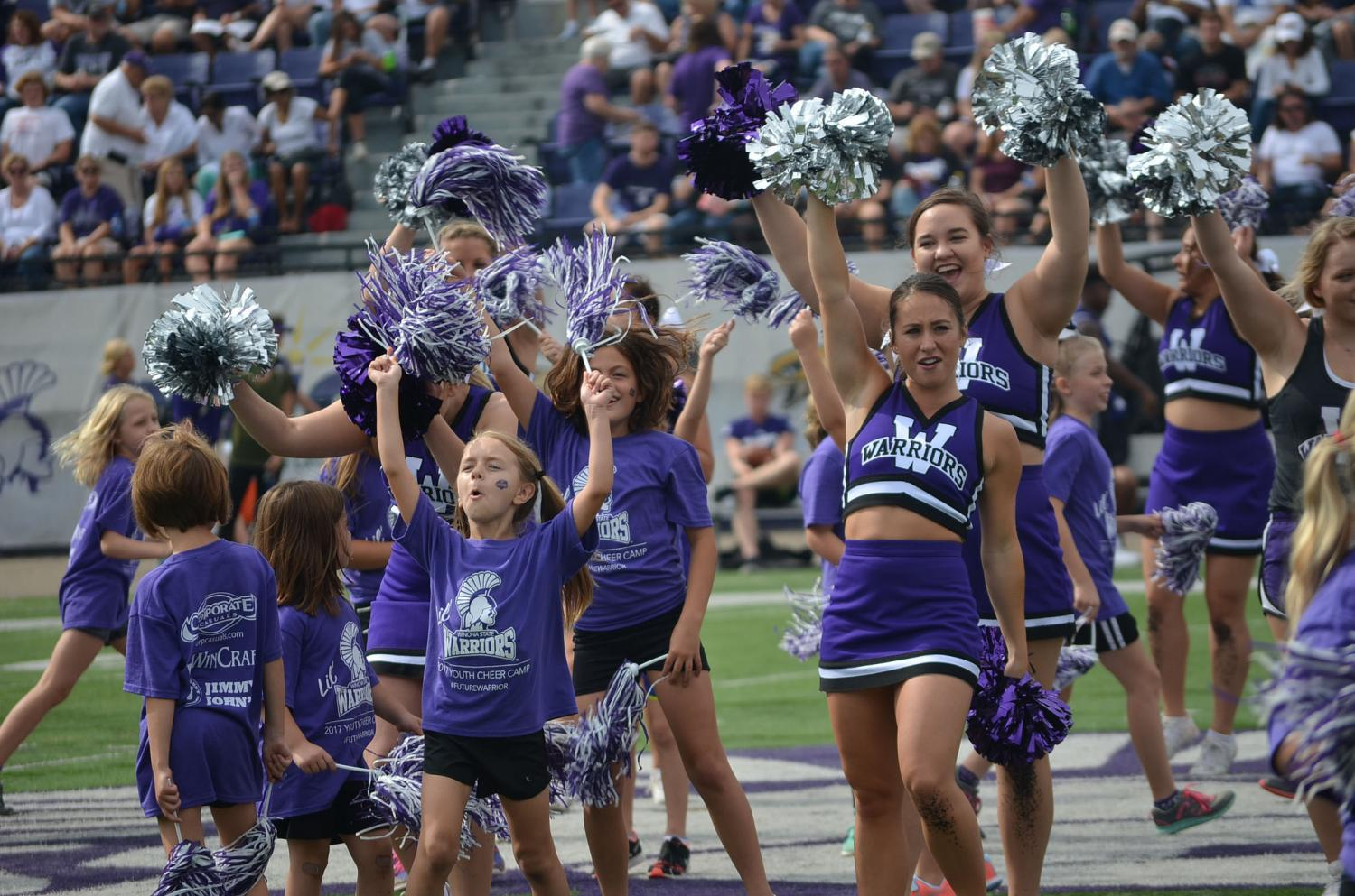 Cheerleader Morgan Anderson cheers along side campers from the annual Warrior Youth Cheer Camp at Saturday, Sept. 17's football game. The camp taught its 65 participants different moves and lifts earlier in the day in McCown Gymnasium. Warrior Youth Cheer Camp is offered to all children, kindergarten through eighth grade.