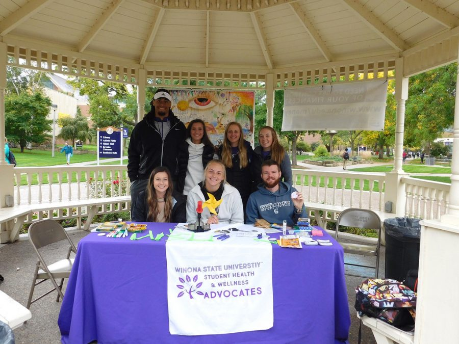 """Back row left to right: Junior Nickolas Pridgeon, sophomore Bridget Doran, junior Courtney Bergum and junior Sidney Brunholzl Front row left to right: Junior Shannon Brohan, first year Raven Ferry-LeClair and junior Jake Dotseth hand out ribbons for mental health awareness in the gazebo last Thursday, Oct. 12 for """"Step Out of Stigma Week""""."""