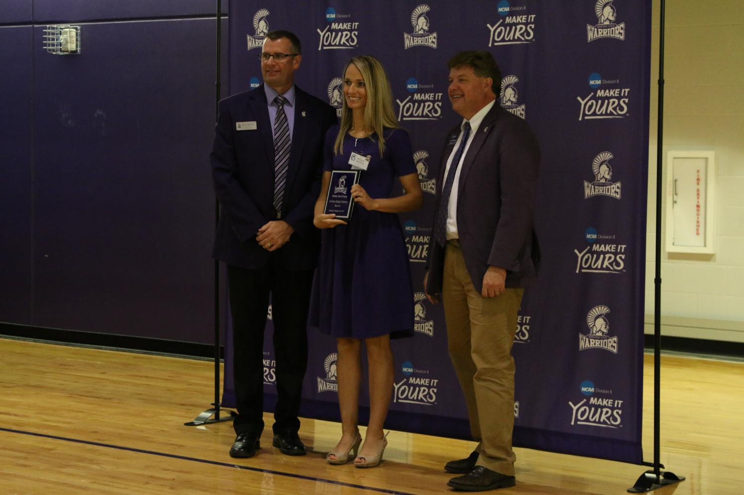 Emily (King) Callender, a former soccer player and the class of 2008, stands with the Athletic Director, Eric Schoh, and President Scott Olson as she is inducted into the Winona State Hall of Fame.