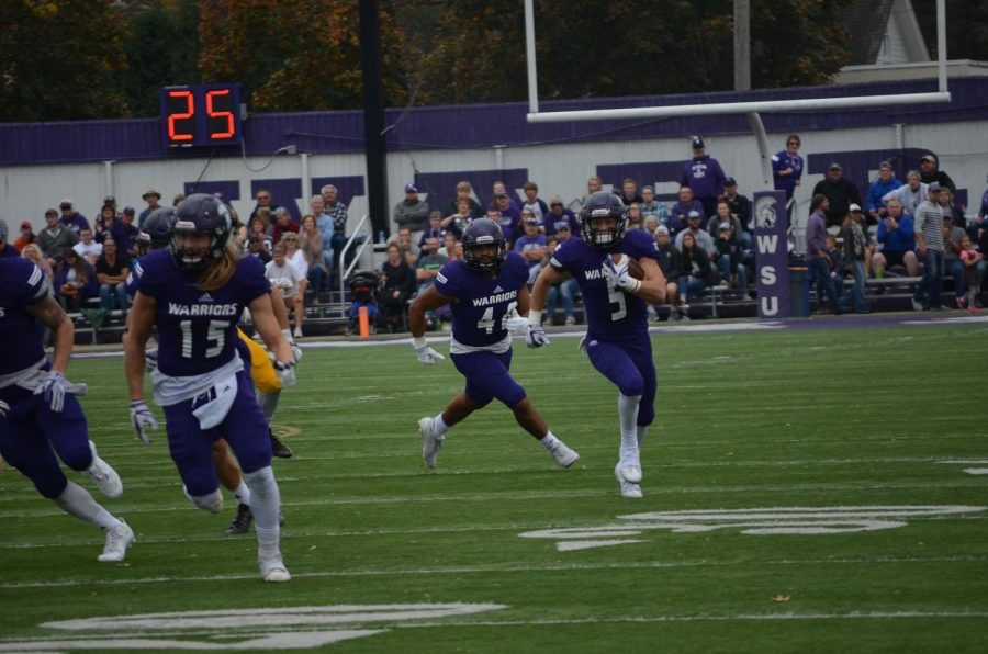 Sophomore Jake Balliu runs down the field towards the end zone on Saturday, Oct. 21's game against Wayne State College in Altra Credit Federal Union Stadium.