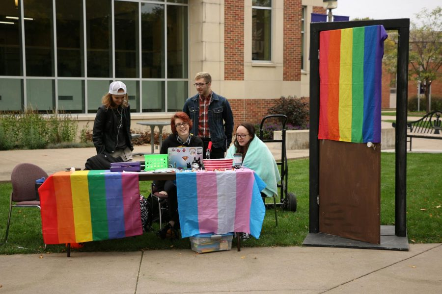 """Members of the student group Full Spectrum tended a table on campus for National Coming Out Day on Wednesday, Oct. 11. The club set up a door next to the table and encouraged people to ceremonially """"come out of the closet"""" by walking through the doorway."""