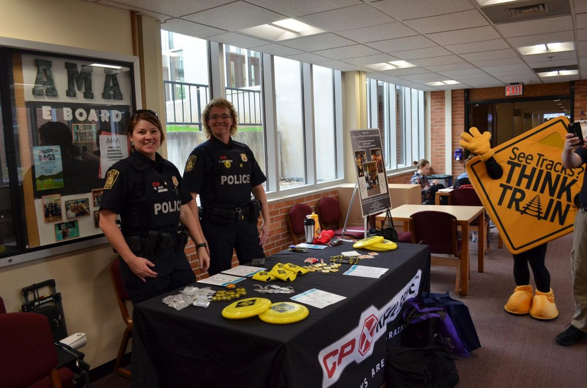 Left to right: Officers Michele Mair and Tracy Bergerson join forces with members of Minnesota Operation Lifesaver volunteers to educate Winona State students on train safety. At the table students could answer trivia questions on a variety of train safety facts to win a prize.