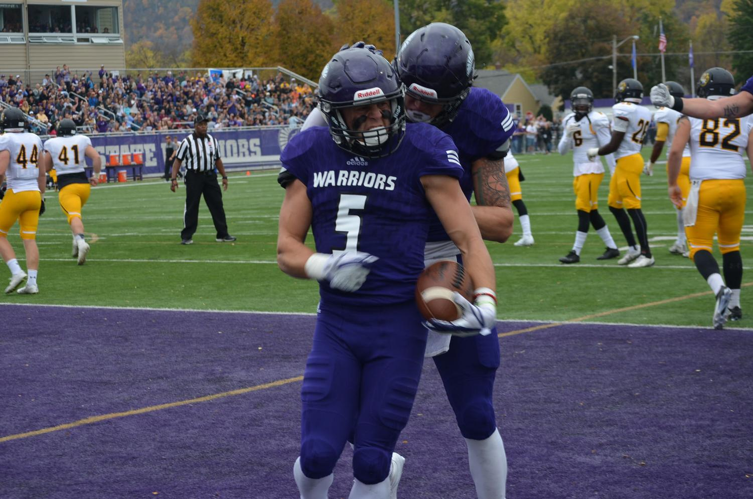 Sophomore Jake Balliu celebrates a touchdown with a teammate at the Homecoming game against Wayne State College on Saturday, Oct. 21 at Altra Credit Federal Union Stadium. The football team won against Southwest Minnesota State University last week, the Warriors play their last game of the regular season at home this Thursday at 7 p.m.