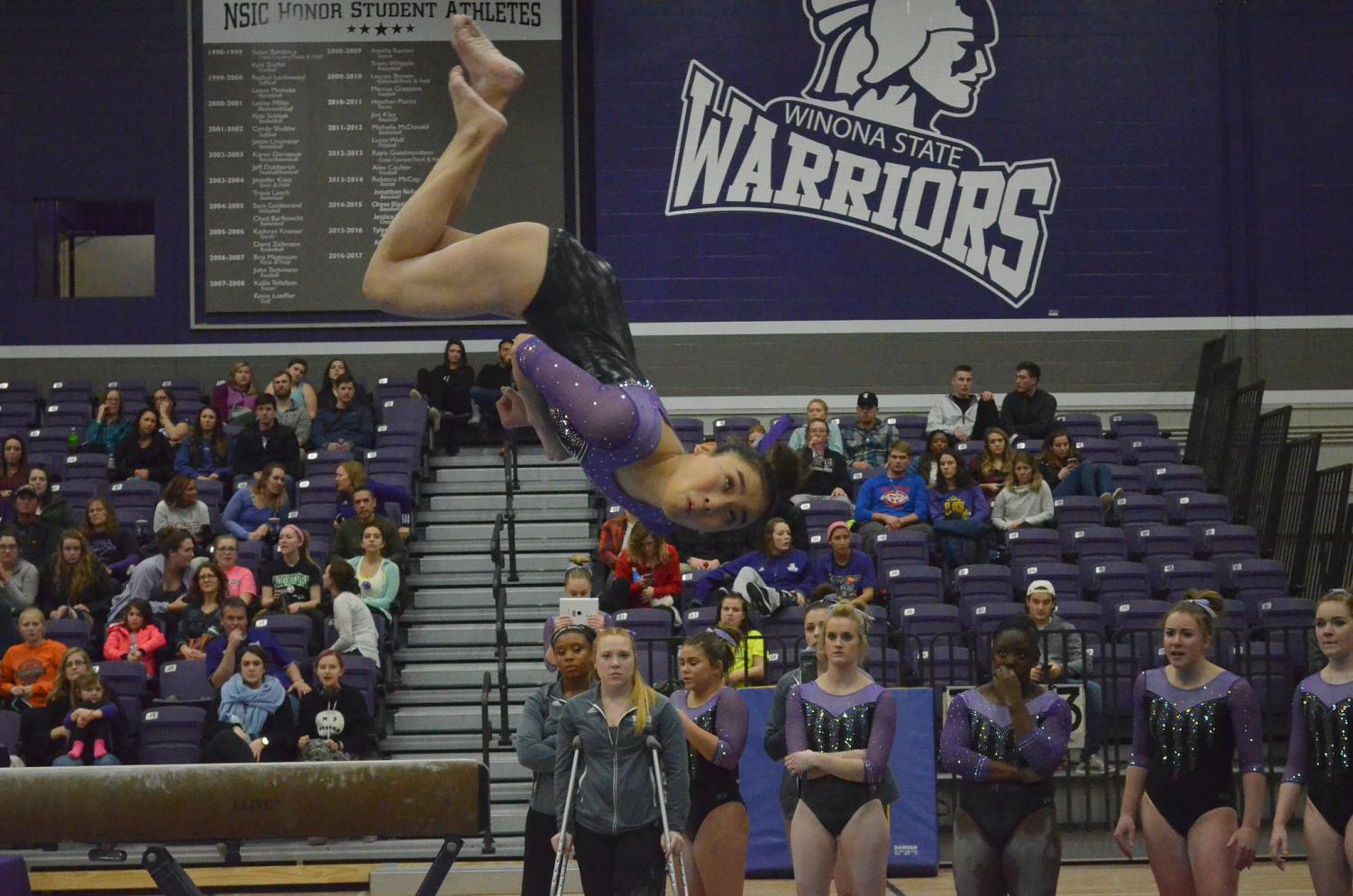 Sophomore Sunny Hasebe dismounts after completing her beam routine during Friday's meet against the University of Wisconsin-Oshkosh in McCown Gymnasium. The Warriors won 185.875-181.4.