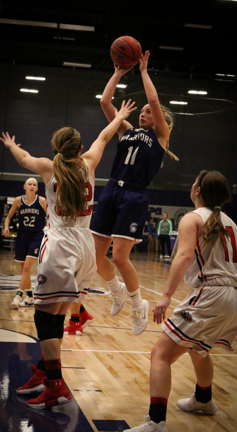 First year center Emily Kieck scores a jumpshot over St. Cloud defendent, Amanda Christianson, during Saturday night's game in McCowan Gymnasium. The Warriors lost to the Huskies 55-62.