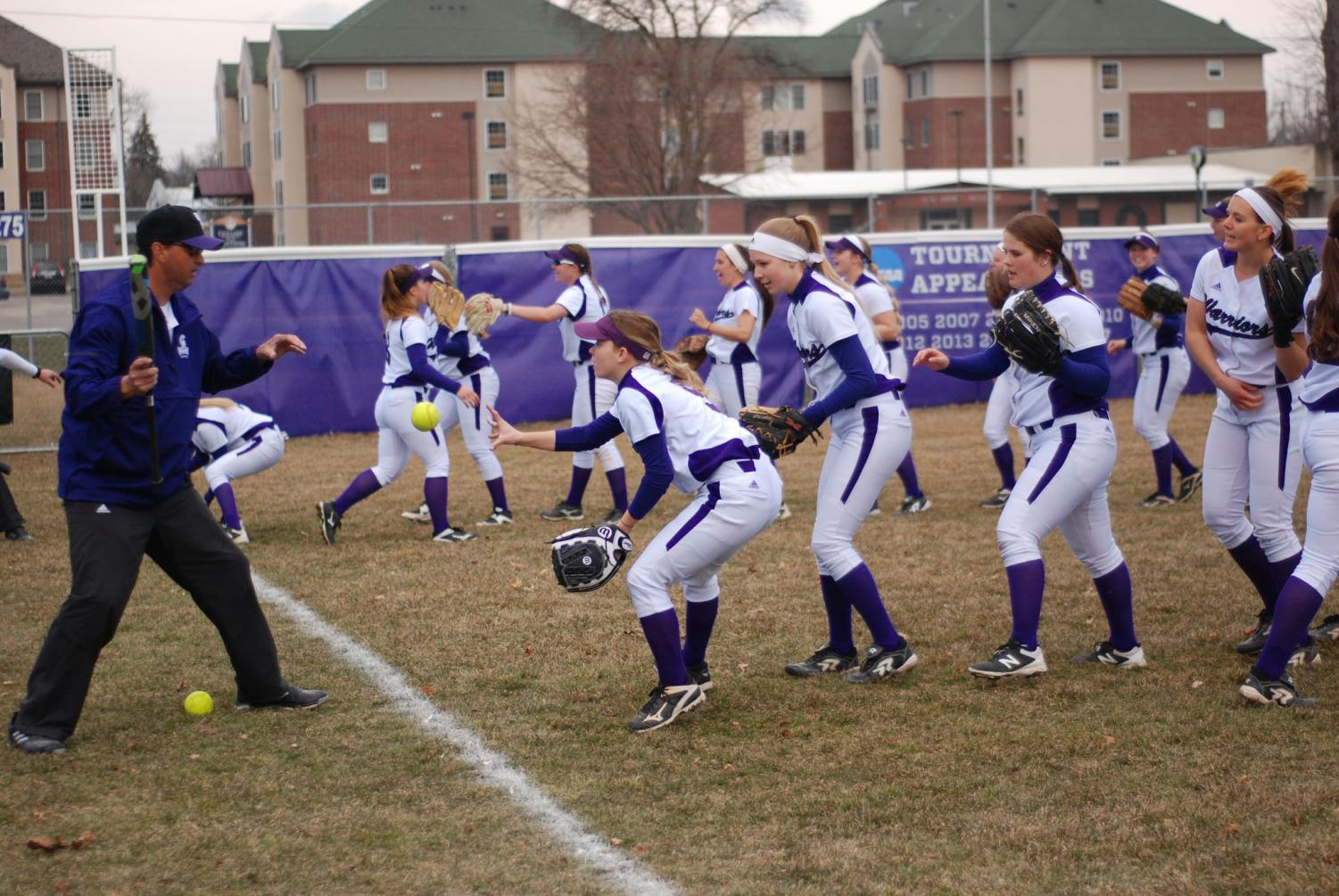 The Winona State Women's Softball Team warm up before a game against St. Cloud State University on Friday, April 12. The Warriors played a double header against the Huskies, loosing their first game 1-3 and coming back with a 3-2 win.