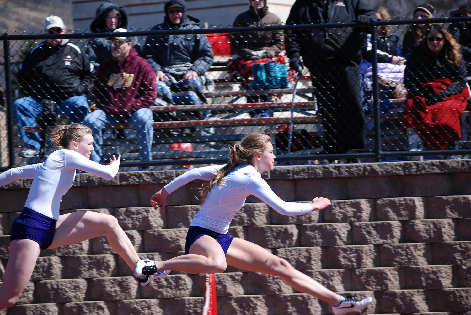 Left to right: Sophomore Kacey Davit and Senior Olivia Fixsen leap over hurdles during the Dingels/Brueggen Open on Thursday, March 29 at Saint Mary's University where the Warriors claimed eight first-place finishes.
