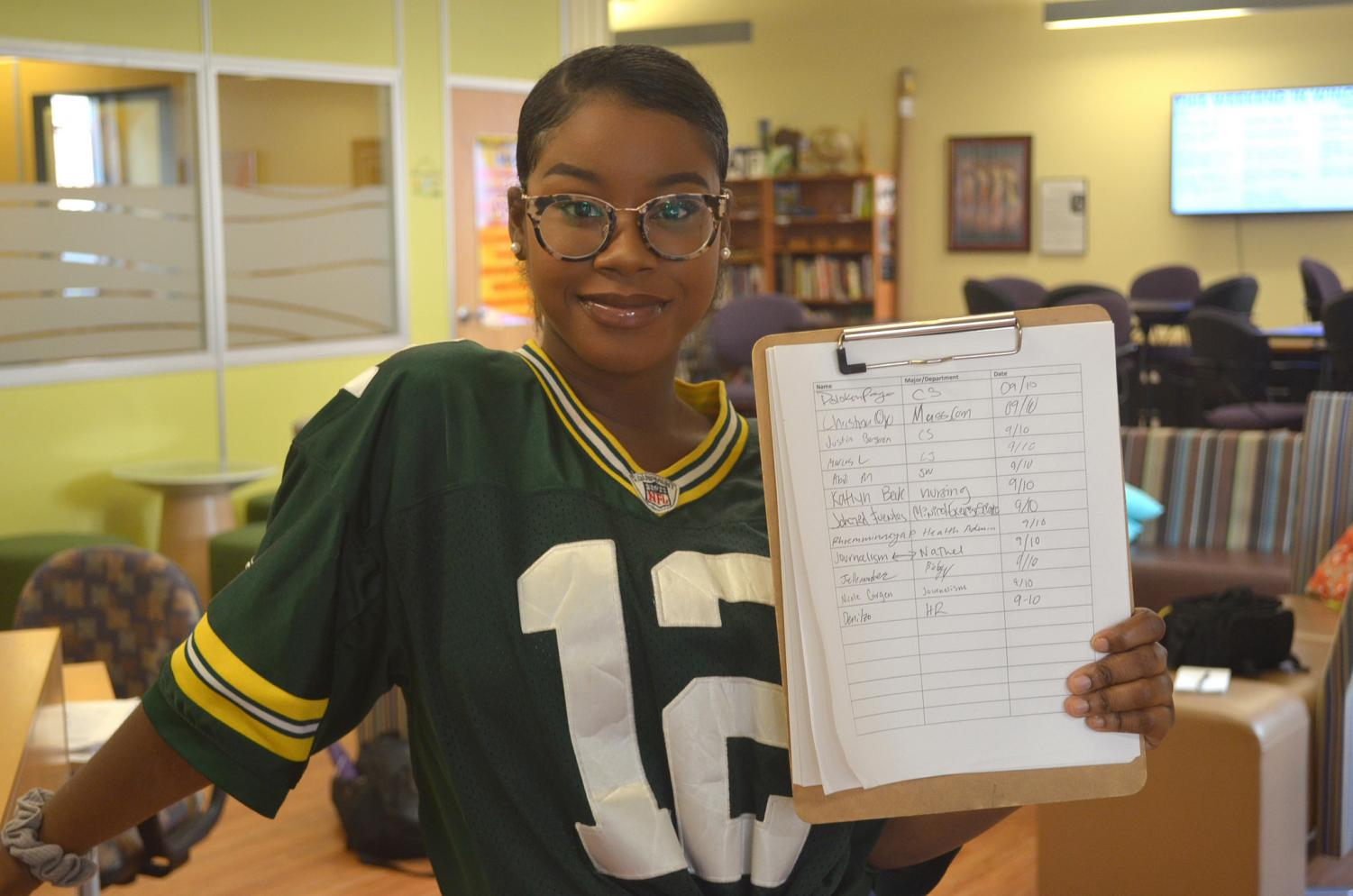 "Senior history and social studies education major Mercedes Williams holds the KEAP Center's sign-in sheet. ""I think its unfair that students need to prove they use this space when clubs like UPAC or spaces like the meditation room don't need that, [the university] just assumes [they're used]."""