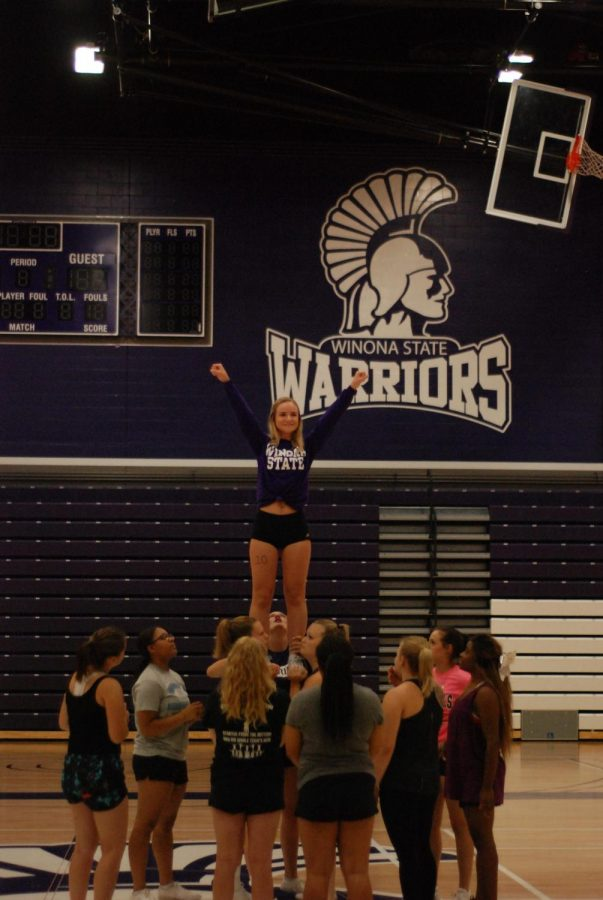 Grace Florin practices a routine as a flyer during the Winona State Cheer Team's tryouts in the McCowan Gymnasium on Thursday, Aug. 30.