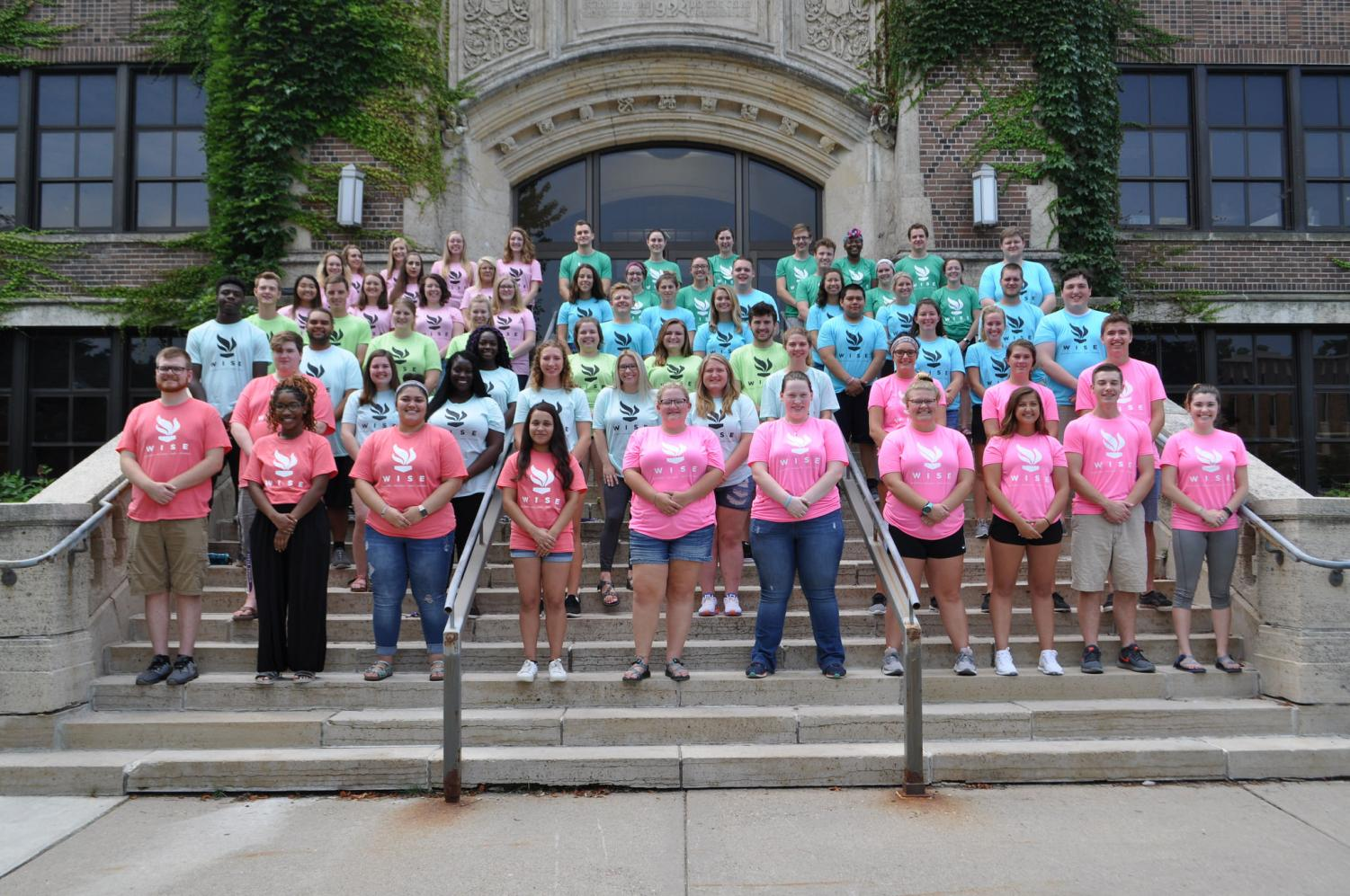 New RAs stand outside of Somsen Hall during their training week, their shirts display the new WISE logo which represents Housing's mission statement of being welcoming, inclusive, safe and engaging and each building staff received a different color.
