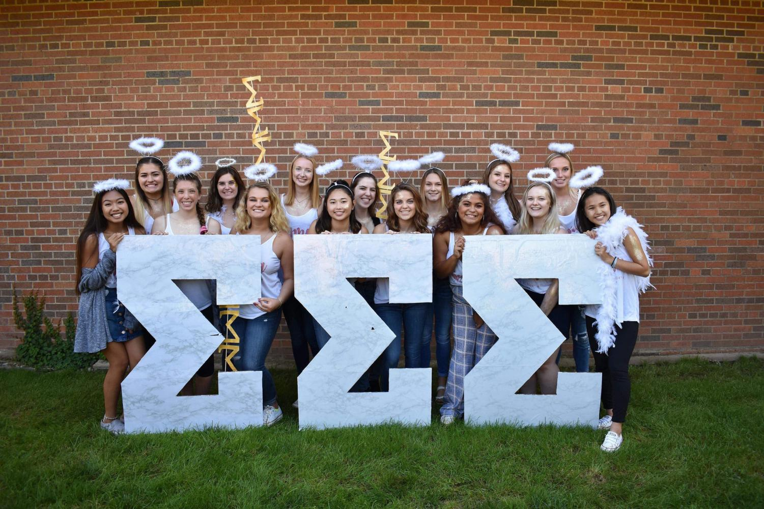 The new members of Tri Sigma pose behind their greek letters during the Bid Day celebration at the Gazebo on Sunday, Sept. 9.