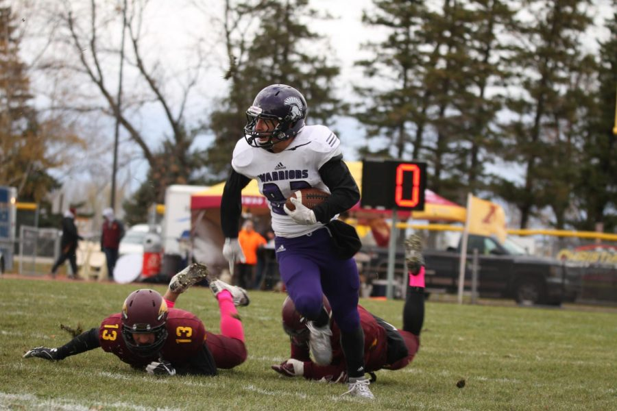 Senior tight end Greg Rooney breaks away from the University of Minnesota Crookston players on Saturday, Oct. 13 where the Warriors won 51-13 bringing the team's overall season record to five wins and two losses.