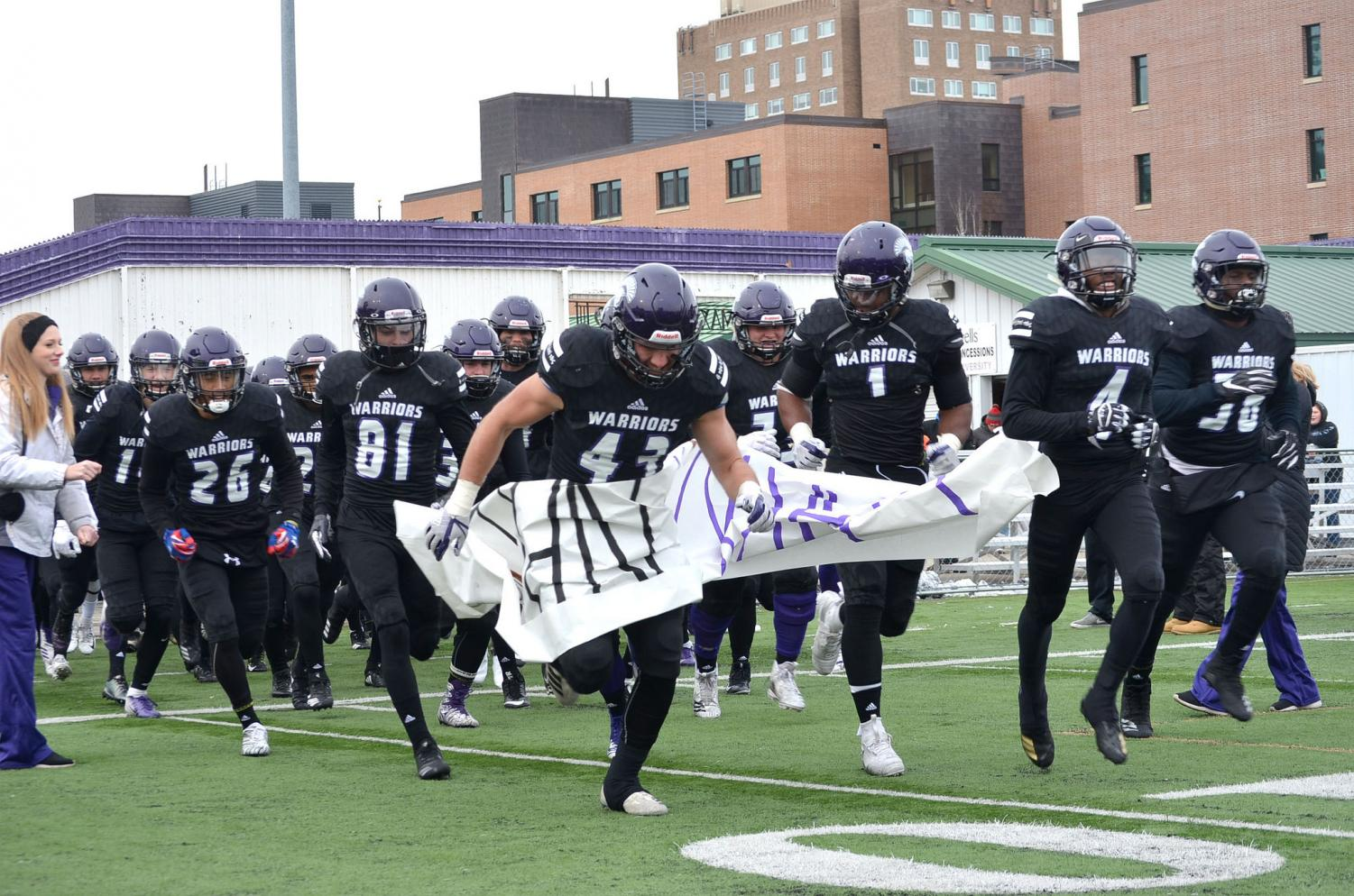 Players charge onto the field, ripping through the banner for the last time this year on Saturday, Nov. 10. This game served as senior day to honor players and cheerleaders on their last game at Winona State. The Warriors took home a 24-20 win against Concordia University, St. Paul bringing the season record to eight wins and three losses.