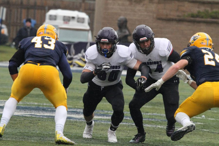 Sophomore wide receiver Ethan Wittenburg moves to block players from Augustana University during a game on Saturday, November 3 where the Warriors won 34-20 against the Vikings.