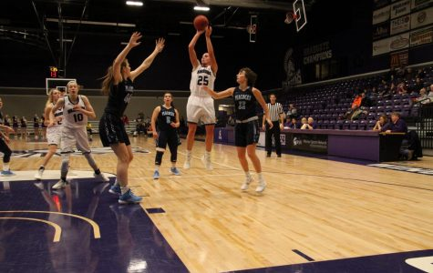 Senior Kayla Shaefer makes a jump shot while being covered by three players from Upper Iowa University during Saturday, Dec. 1's game in McCown Gymnasium. The Warriors finished the game with a winning score of 74-48 bringing their season record to three wins and two losses.