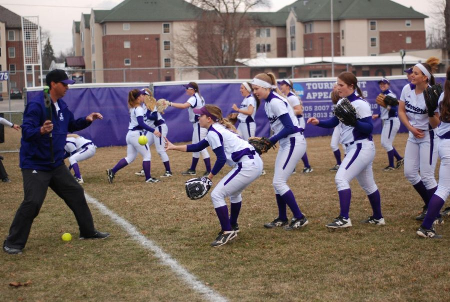 The Winona State softball team warm up before a game against St. Cloud State University last season. The Warriors played a double header against the Huskies, losing their first game 1-3 and coming back with a 3-2 win. Their main priority this season is to bring up their record and work together.