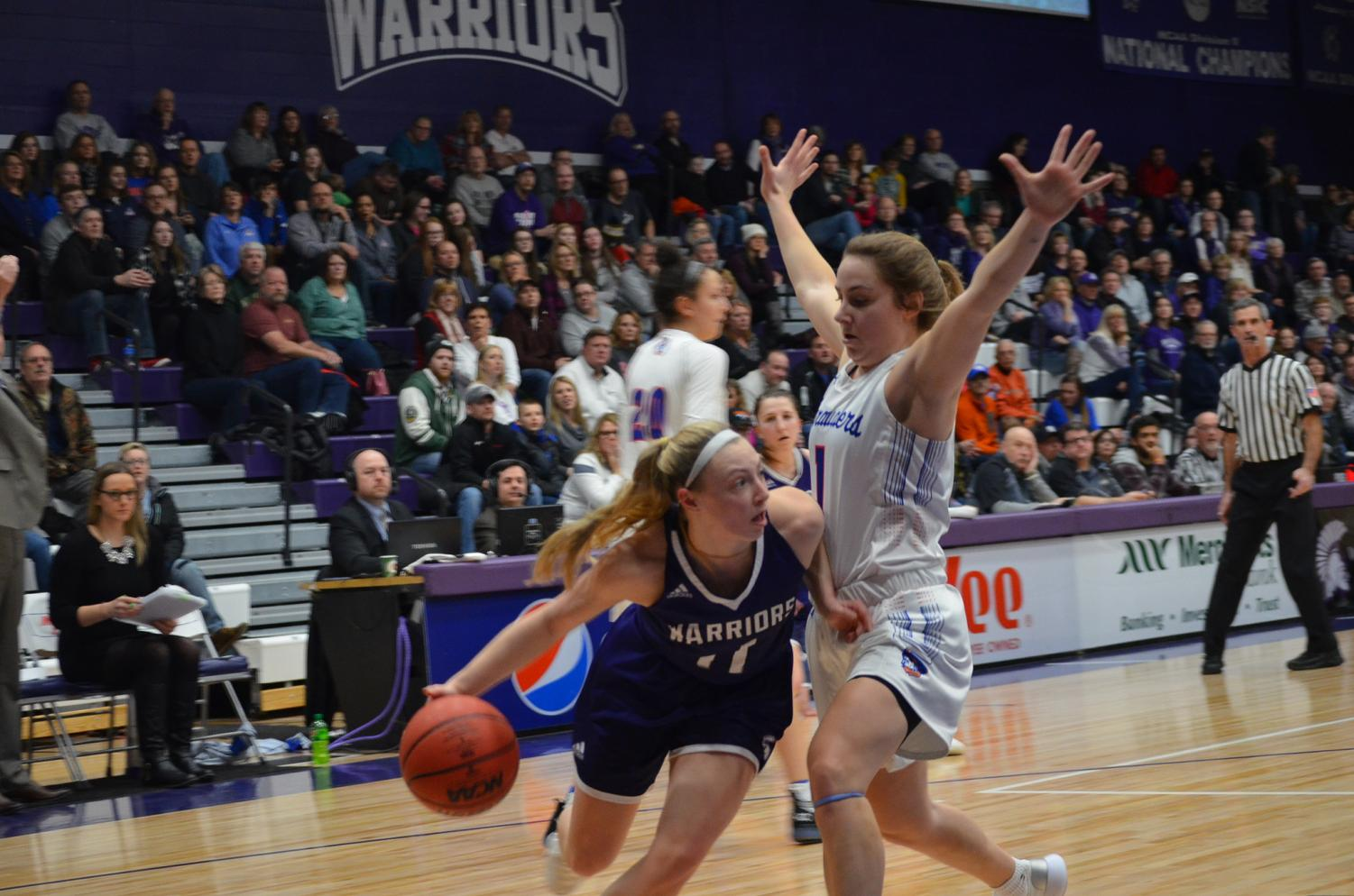 Sophomore Emily Kieck weaves around a University of Mary player on Saturday, February 9 in McCown Gymnasium. The Warriors took home two wins, scoring 84-46 on Friday and 57-54 on Saturday.
