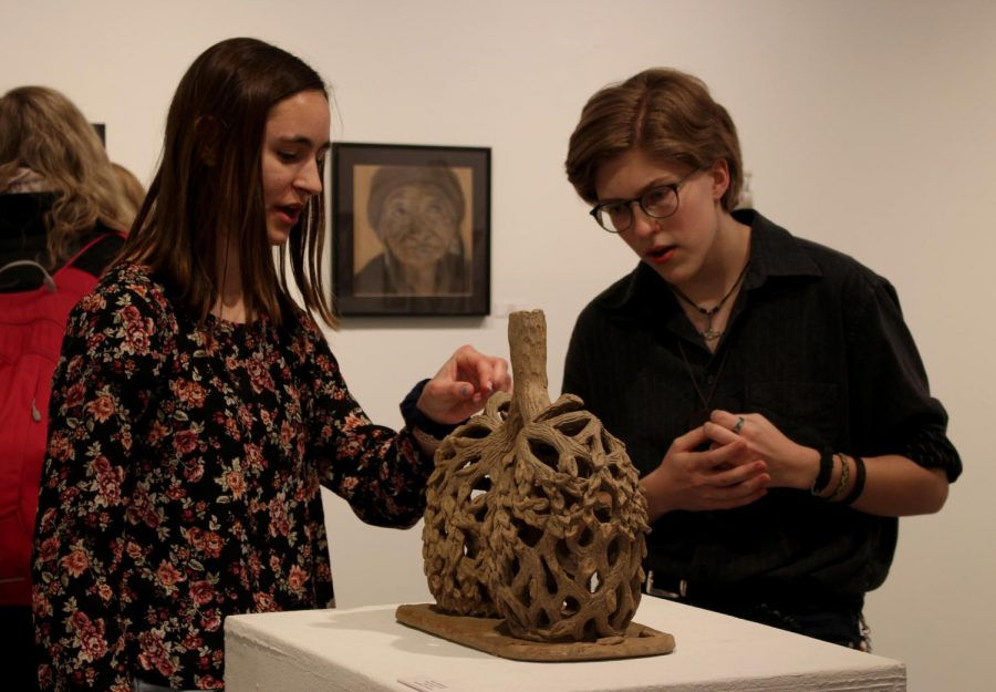 Hailey Hellenbrand (left) explains to Kiri Sannerud how she created her sculpture at Art Muse on Wednesday, March 20 in Watkins Gallery. Hellenbrand's piece was given a second place honorable mention out of the 31 pieces displayed. Over 100 pieces of art were submitted by students to be displayed in the gallery.