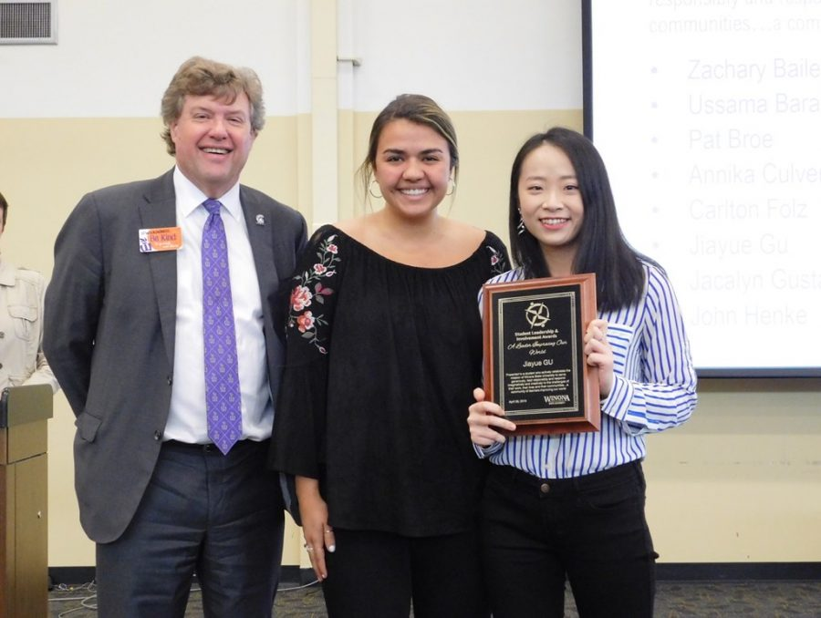 "Jiayue Gu, a senior clinical science major, accepts the ""A Leader Improving Our World"" award from Winona State President Scott Olson and Student Senate President Christina Melecio during the Student Leadership and Involvement Awards on Monday, April 29 in East Hall. Gu won out of 23 nominees for her outstanding work within the campus community in helping international students transition to life in Winona."