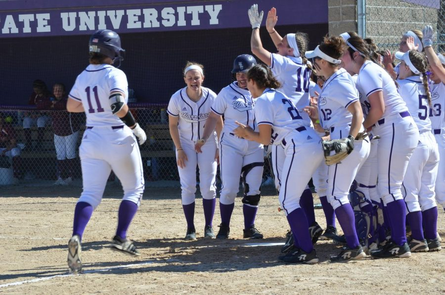 The Winona State softball team lines up along the base line to congratulate junior Alison Nowak on her home run hit against the University of Minnesota Duluth on Friday, April 19 at the Maynard R. Johnson Field.