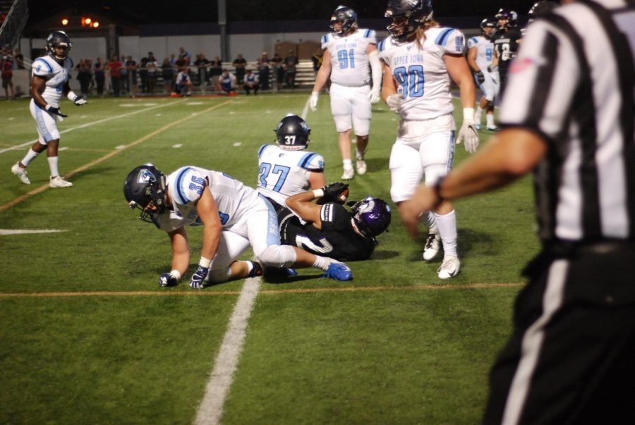 Sam Santiago-Lloyd, a sophomore running back, is tackled on the ground during the first-half by players from Upper Iowa University on Thursday, Sept. 19. The Warriors secured their second win of the season against the Peacocks, scoring 28-0 at Altra Credit Federal Union Stadium.