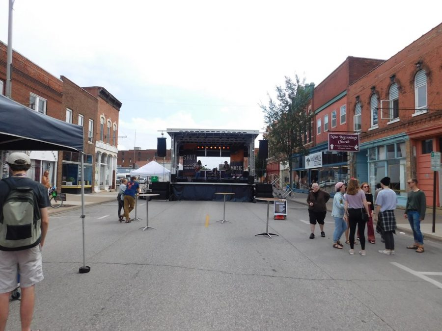 """Afflatus tuning up and preparing for their performance at """"Shut Down Third Street."""" Guests mingled around the stage and in local shops as they wait for the band's performance to start."""
