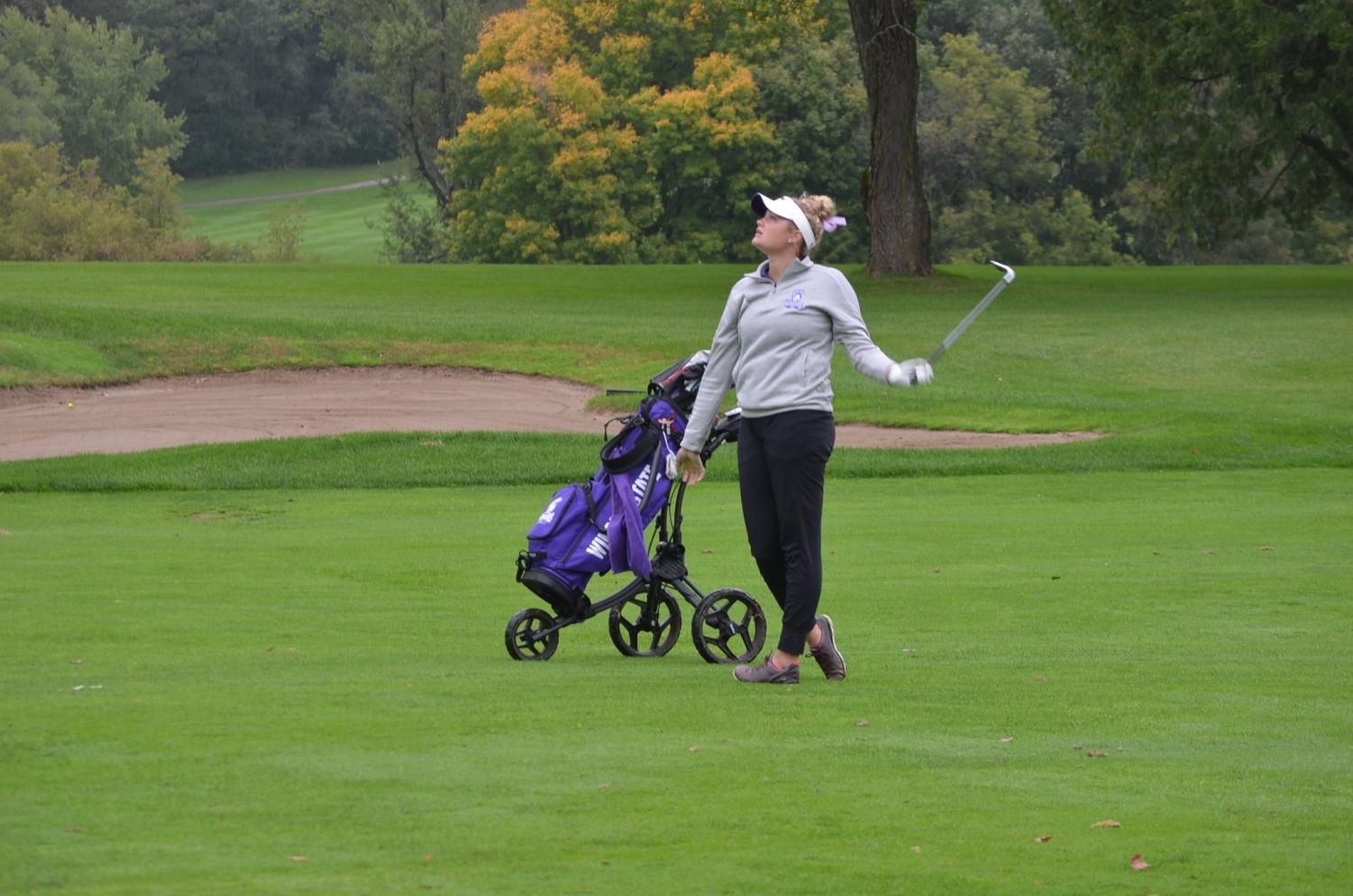 Sophomore Ally Loiselle watches for her ball during a duel against Viterbo University on Sunday, Sept. 29 at the Bridges Golf Course in Winona. The Warriors won with a team score of 321-334.