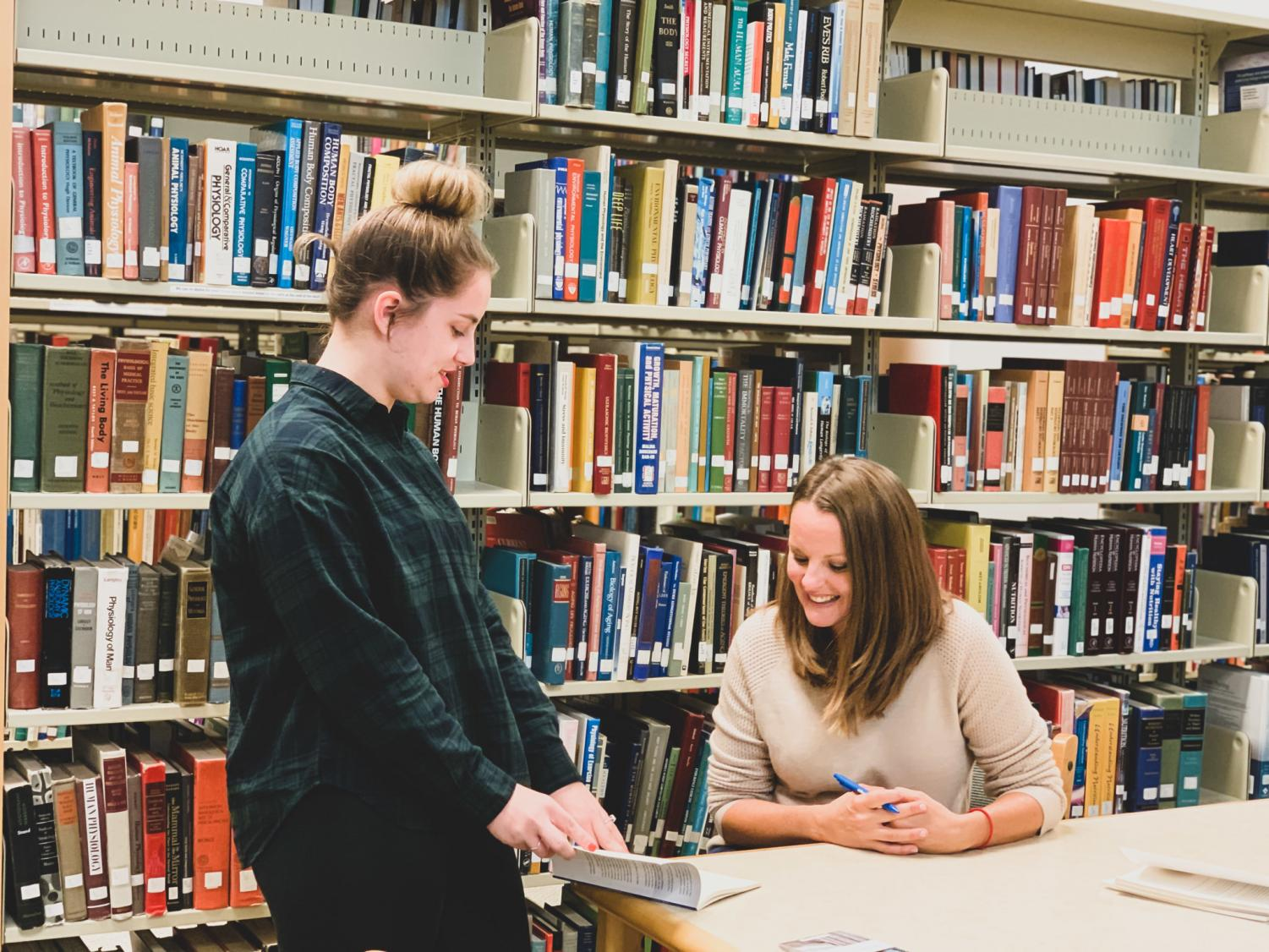 "Crystal Spring Gibbins signs her book ""Now/Here"" during a meet and greet with students after finishing a reading session at the Darrell W. Krueger Library on Thursday, Oct. 3."