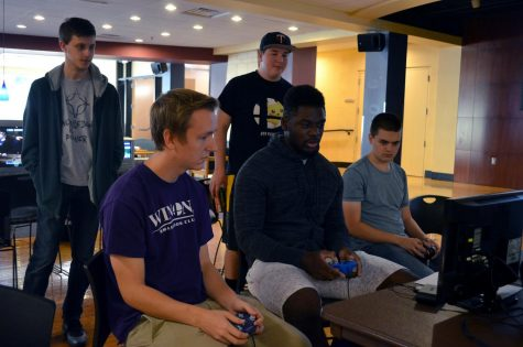 Club members watch as junior Trevor Firo and first-year Loic Boyogueno play Super Smash Bros. during a club tournament on Saturday, Sept. 28 in the Student Activities Center.
