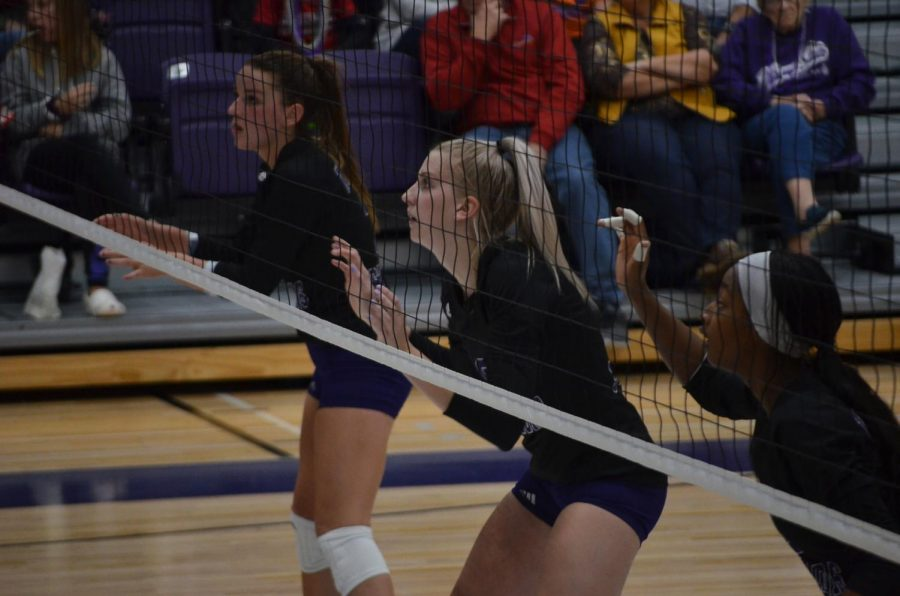 Left to right: Bre Maloney, Megan Flom and Paige Christopher get ready to block a hit during the game against Augustana University on Saturday, October 12.