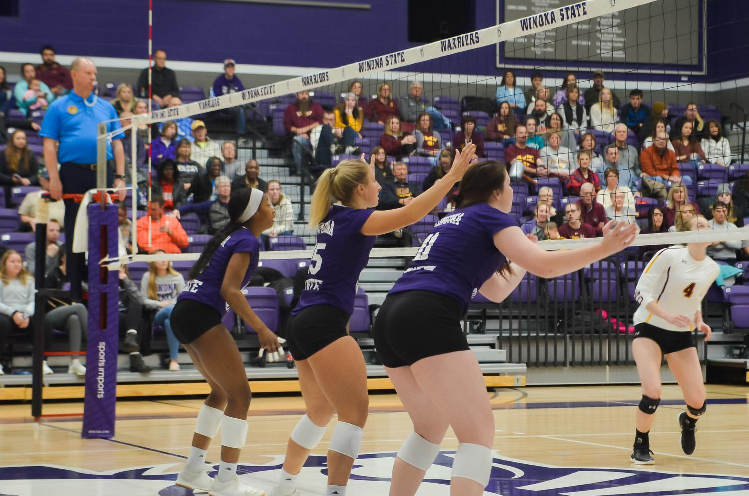 Left to right: Paige Christopher, Madison Rizner and Kate Masberg guard the net against the University of Minnesota Duluth on Saturday, Nov. 16 in McCown Gymnasium. After the win this weekend the Warriors head into the NSIC Tournament with a season record of 21-7.