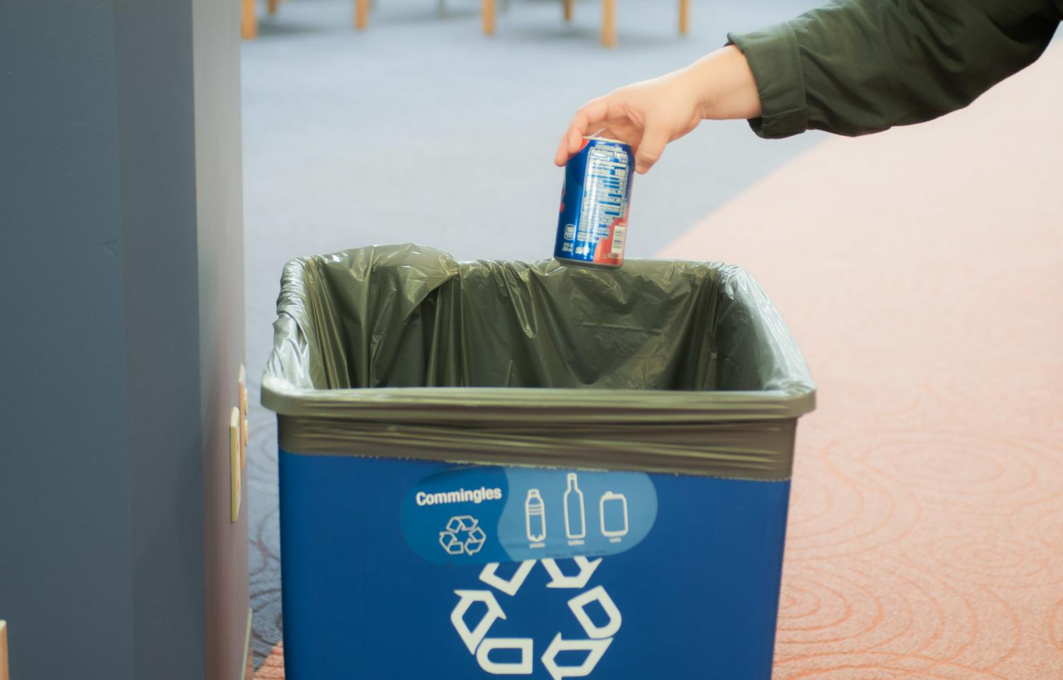 A student using one of the many recycling bins on campus. According to Nathan Engstrom, Director of sustainability at Winona State University, by spring semester they wish to use a different style of signage for the new containers.