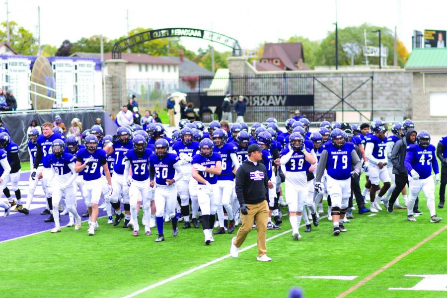 Winona State Warriors heading off-field after a group huddle before the game. The Warriors faced Minot State University Beavers on Sunday, October 13 for the Homecoming game. The Warriors won 49-3 despite a day-delay of the game and 37-degree weather.