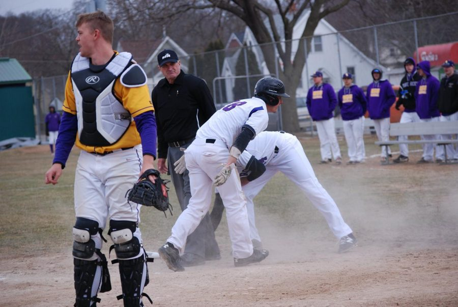 Senior Taylor Field is congratulated by a teammate after completing a full run against Minnesota State University Mankato last season on Tuesday, March 27 at Loughrey Field.