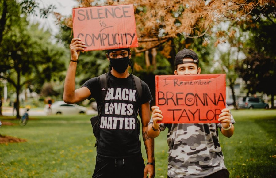 Brian Payton (left) and Cameron Womack (right), Winona State seniors, hold their signs at the Black Lives Matter protest at Windom Park, on Tuesday, Sept 1. People of all races came together to peacefully protest police brutality on black lives.