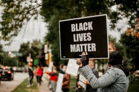 A protestor holding a Black Lives Matter (BLM) sign at Windom Park, on Tuesday, Sept. 1.  A group of people took part in a peaceful protest led by Eileen Hanson. The protest Black Lives Matter supports people of color fighting police brutality. Specific names in context come up including George Floyd, Breonna Taylor, and many more. The motorists passing by expressed support by honking.