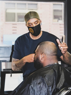 Gilbert Jordan IV, or more commonly known as Uncle Gil giving a  haircut to Kevin Suber in his newly opened barbershop, called Uncle Gil's Cutz, located located in the Kensington building in Winona, Minn.